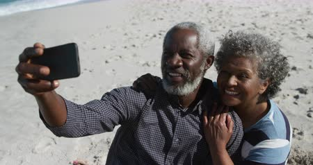 fotoğraflar : High angle side view of a senior African American couple sitting on the beach with sea in the background, embracing and smiling, the man taking selfies with smartphone in slow motion Stok Video