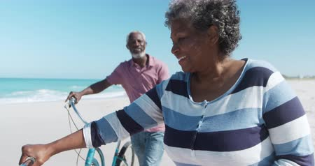 Деятельность выходные : Front view of a senior African American couple walking with bikes on the beach with blue sky and sea in the background talking in slow motion Стоковые видеозаписи