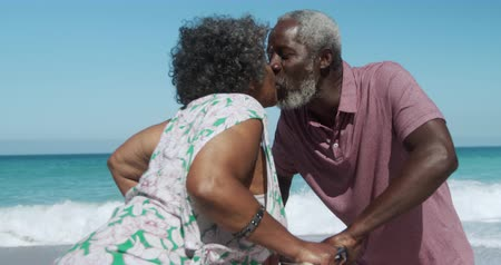 pocałunek : Side view of a senior African American couple standing on the beach with their bicycles with blue sky and sea in the background, kissing in slow motion