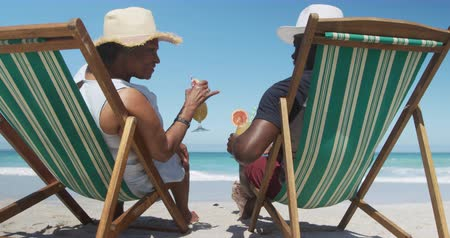 Деятельность выходные : Rear view of a senior African American couple sitting in deckchairs on the beach with blue sky and sea in the background, drinking cocktails in slow motion Стоковые видеозаписи