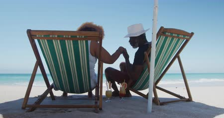 náklonnost : Rear view of a senior African American couple sitting in deckchairs under parasol on the beach with blue sky and sea in the background, man kissing hand of the woman in slow motion Dostupné videozáznamy