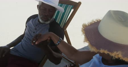 pocałunek : Side view close up of a senior African American couple sitting in deckchairs on the beach, man kissing hand of the woman  in slow motion