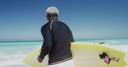 Деятельность выходные : Side view of a senior African American man on a beach in the sun, running and carrying a surfboard under his arm, with blue sky and sea in the background in slow motion