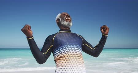 emelt : Front view of a happy senior African American man on a beach in the sun, wearing a wetsuit, raising his fists and laughing wearing a wetsuit, with blue sky and sea in the background in slow motion