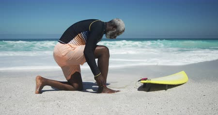 уик энд : Side view of a senior African American man on a beach in the sun, preparing before surfing with blue sky and sea in the background in slow motion