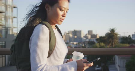 individualidade : Side view of a mixed race woman with long dark hair out and about in the city streets during the day, walking in a street, holding a cup of takeaway coffee and using a smartphone with buildings in the background in slow motion.