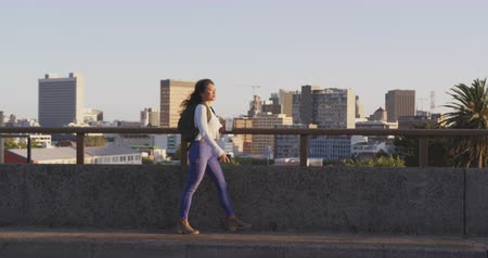 individualidade : Side view of a mixed race woman with long dark hair out and about in the city streets during the day, walking in a street, holding a cup of takeaway coffee and a smartphone with buildings in the background in slow motion. Stock Footage
