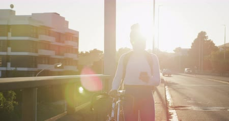 schrikken : Front view of a mixed race woman with long dark hair out and about in the city streets during the day, wearing a face mask against air pollution and coronavirus, walking with her bicycle and using a smartphone with urban road traffic in the background in  Stockvideo