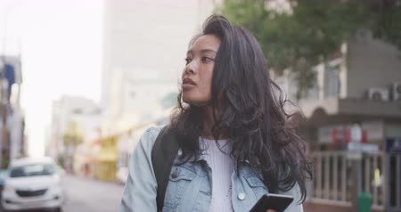 individualidade : Front view of a mixed race woman with long dark hair out and about in the city streets during the day, standing in a street and using a smartphone with buildings in the background in slow motion.