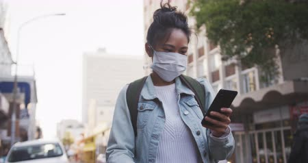 baixo ângulo : Low angle front view of a mixed race woman with long dark hair out and about in the city streets during the day, wearing a face mask against air pollution and coronavirus, walking with her bicycle and using a smartphone with urban road traffic in the back Stock Footage