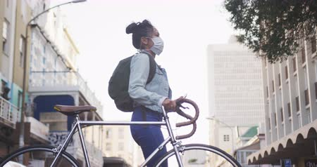 dojíždění : Low angle side view of a mixed race woman with long dark hair out and about in the city streets during the day, wearing a face mask against air pollution and coronavirus, walking with her bicycle and using a smartphone with buildings in the background in