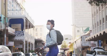 schrikken : Side view of a mixed race woman with long dark hair out and about in the city streets during the day, wearing a face mask against air pollution and coronavirus, walking with her bicycle and using a smartphone with urban road traffic in the background in s