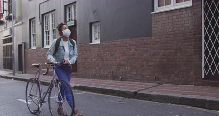 dojíždění : Side view of a mixed race woman with long dark hair out and about in the city streets during the day, wearing a face mask against air pollution and coronavirus, walking with her bicycle with buildings in the background in slow motion.