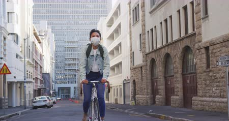 individualidade : Front view of a mixed race woman with long dark hair out and about in the city streets during the day, wearing a face mask against air pollution and coronavirus, riding on her bicycle with buildings in the background in slow motion.