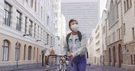 dojíždění : Front view of a mixed race woman with long dark hair out and about in the city streets during the day, wearing a face mask against air pollution and coronavirus, walking with her bicycle with buildings in the background in slow motion.