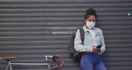 ciclismo : Front view of a mixed race woman with long dark hair out and about in the city streets during the day, wearing a face mask against air pollution and coronavirus, standing next to her bicycle and using a smartphone with grey shutters in the background in s Stock Footage