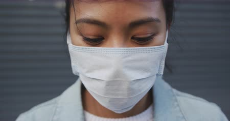dojíždění : Portrait close up of a mixed race woman with dark hair out and about in the city streets during the day, wearing a face mask against air pollution and coronavirus, standing and looking at camera with grey wall in the background in slow motion.