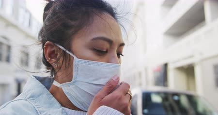 dojíždění : Side view of a sick mixed race woman with long dark hair out and about in the city streets during the day, wearing a face mask against air pollution and coronavirus, coughing with buildings in the background in slow motion.