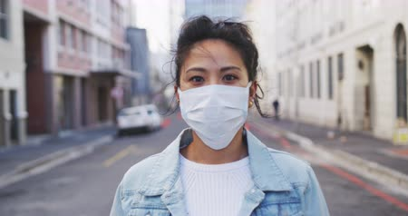 individualidade : Portrait close up of a mixed race woman with dark hair out and about in the city streets during the day, wearing a face mask against air pollution and coronavirus, standing and looking at camera with buildings in the background in slow motion. Stock Footage