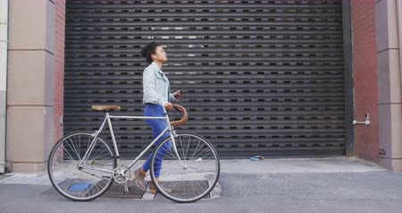 이어폰 : Side view of a mixed race woman with long dark hair out and about in the city streets during the day, walking with her bicycle and using a smartphone with earphones on, with building in the background