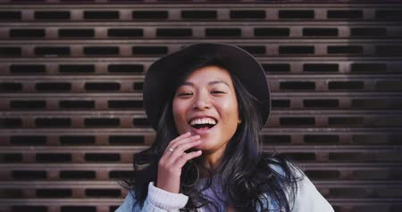 individualidade : Portrait of a happy mixed race woman with long dark hair out and about in the city streets during the day, wearing a hat and denim jacket, smiling to camera with wall in the background in slow motion.