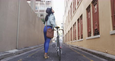 dojíždění : Rear view of a mixed race woman with long dark hair out and about in the city streets during the day, walking with her bicycle in a street with buildings in the background in slow motion.