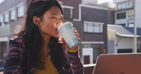 dojíždění : Side view of a mixed race woman with long dark hair out and about in the city streets during the day, sitting in a cafe working on a laptop computer and a smartphone, drinking takeaway coffee with buildings in the background in slow motion.