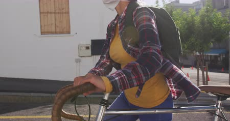 alergia : Side view of a mixed race woman with dark hair out and about in the city streets during the day, wearing sunglasses and a face mask against air pollution and coronavirus, walking with her bike with buildings in the background in slow motion