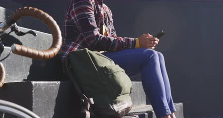 dojíždění : Side view of a mixed race woman with dark hair out and about in the city streets during the day, wearing sunglasses and a face mask against air pollution and coronavirus, sitting on steps using a smartphone, a bike next to her with wall in the background