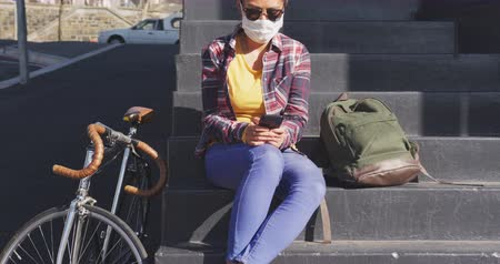 alerji : Front view of a mixed race woman with dark hair out and about in the city streets during the day, wearing sunglasses and a face mask against air pollution and coronavirus, sitting on steps using a smartphone, a bike next to her with traffic in the backgro Stok Video