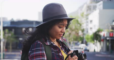 dojíždění : Side view of a happy mixed race woman with long dark hair out and about in the city streets during the day, walking with headphones on, listening to music, holding a smartphone, smiling with buildings in the background in slow motion.