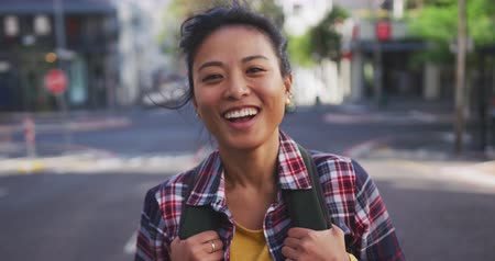 individualidade : Portrait of a happy mixed race woman with long dark hair out and about in the city streets during the day, carrying a backpack, wearing a checked shirt, smiling to camera with buildings in the background in slow motion.