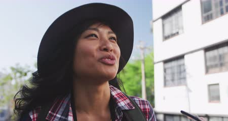 dojíždění : Low angle side view of a happy mixed race woman with long dark hair out and about in the city streets during the day, walking wearing a hat and checked shirt, talking on the smartphone with buildings in the background in slow motion.