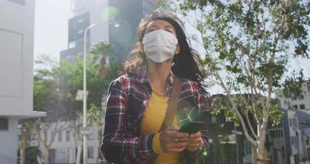 baixo ângulo : Low angle side view of a mixed race woman with long dark hair out and about in the city streets during the day, wearing a face mask against air pollution and coronavirus, walking in a city street and using a smartphone with buildings in the background in  Stock Footage