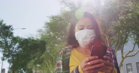 filtro aire : Low angle front view of a mixed race woman with long dark hair out and about in the city streets during the day, wearing a face mask against air pollution and coronavirus, walking in a city street and using a smartphone with buildings in the background in Archivo de Video