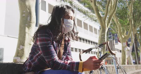 individualidade : Low angle side view of a mixed race woman with dark hair out and about in the city streets during the day, wearing a face mask against air pollution and coronavirus, sitting on steps using a smartphone, a bike next to her with buildings in the background  Stock Footage