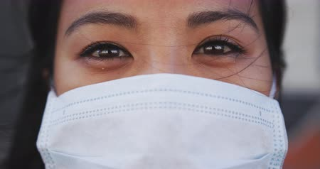 dojíždění : Portrait close up of a mixed race woman with dark hair out and about in the city streets during the day, wearing a face mask against air pollution and coronavirus, looking at camera in slow motion. Dostupné videozáznamy