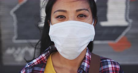 dojíždění : Portrait of a mixed race woman with dark hair out and about in the city streets during the day, wearing a face mask against air pollution and coronavirus, looking at camera in slow motion.