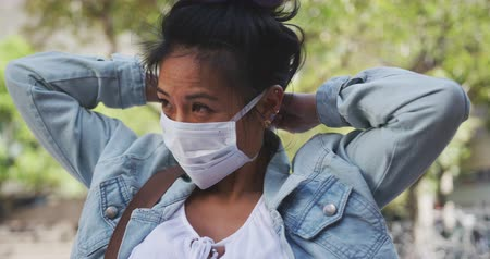 dojíždění : Side view of a mixed race woman with dark hair out and about in the city streets during the day, wearing a face mask against air pollution and coronavirus, standing and fastening her face mask with trees in the background in slow motion. Dostupné videozáznamy