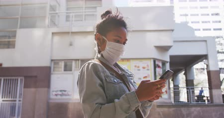 dojíždění : Side view of a mixed race woman with dark hair out and about in the city streets during the day, wearing a face mask against air pollution and coronavirus, using a smartphone with buildings in the background in slow motion. Dostupné videozáznamy