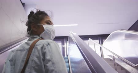 dojíždění : Low angle rear view of a mixed race woman with long dark hair out and about in the city streets during the day, wearing a face mask against air pollution and coronavirus, standing on escalator looking around in slow motion