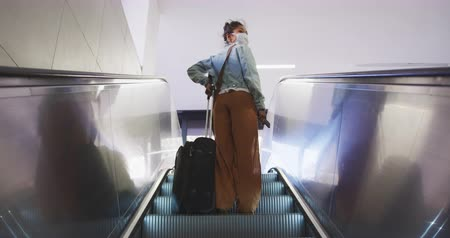 baixo : Low angle rear view of a mixed race woman with long dark hair out and about in the city streets during the day, wearing a face mask against air pollution and coronavirus, standing on escalator with a suitcase looking around in slow motion