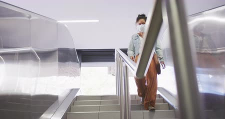 escalators : Low angle front view of a mixed race woman with long dark hair out and about in the city streets during the day, wearing a face mask against air pollution and coronavirus, walking down a staircase in slow motion Stock Footage