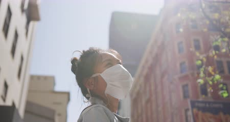 baixo ângulo : Low angle side view of a mixed race woman with dark hair out and about in the city streets during the day, wearing a face mask against air pollution and coronavirus, standing in a street with buildings in the background in slow motion.