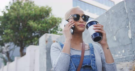 kısa : Low angle front view of happy mixed race woman with short dyed blonde hair out and about in the city on a sunny day, talking on her smartphone, wearing sunglasses and drinking takeaway coffee with building in the background in slow motion. Stok Video
