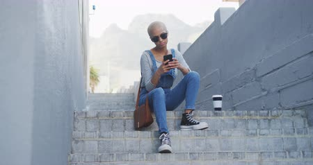 kısa : Front view of happy mixed race woman with short dyed blonde hair out and about in the city on a sunny day, using her smartphone sitting on steps wearing sunglasses in slow motion.