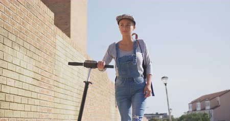 kısa : Front view of happy mixed race woman out and about in the city on a sunny day, wearing a cap, walking with her electric scooter on a road with buildings in the background in slow motion.