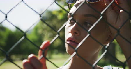 látszó el : Front view close up of happy mixed race woman with short dyed blonde hair out and about in the city on a sunny day, seen through a fence, taking her sunglasses off, standing by a fence looking away in slow motion. Stock mozgókép