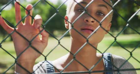 visto : Portrait close up of happy mixed race woman with short dyed blonde hair out and about in the city on a sunny day, seen through a fence, standing by a fence looking at camera in slow motion. Stock Footage