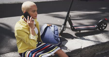 call out : Front view of happy mixed race woman with short dyed blonde hair out and about in the city on a sunny day, talking on her smartphone, electric scooter next to her in slow motion.